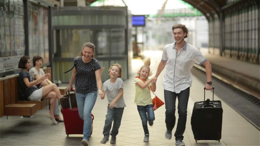 Young family of two spouses, son and daughter, running to catch the train before it leaves the railway station without them, parents and children traveling and be late
