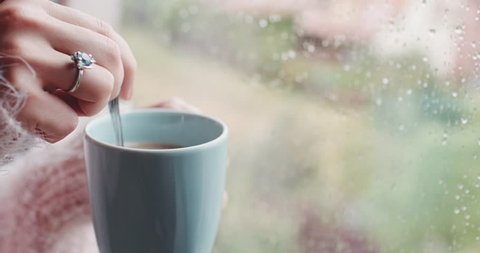 Female Hand Stirring Sugar or Milk in a cup of Hot Coffee or Tea, Rainy Window Background. 4K DCi SLOW MOTION 120 fps. Having Morning coffee by the window, in rainy spring, winter or autumn day.