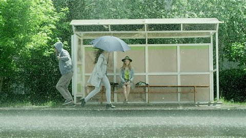 Girl sitting at the bus stop in the rain. People running in the rain with umbrellas. Shot on RED EPIC Cinema Camera in slow motion.