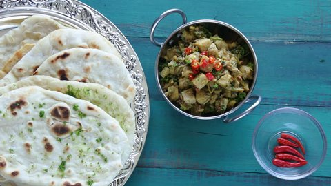 Flat lay view of Indian woman hands serve Alu Methi with Naan flatbread and fresh chilli.Food background of West, Central and South Asia cuisines. copy space
