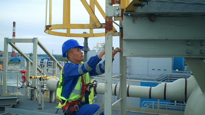 Asian engineer climbing the tower of a large oil refinery
