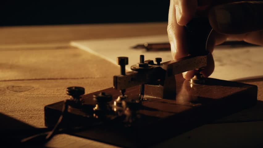 dolly closeup of a telegrapher using a morse code key 4k