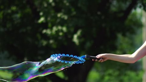 Create a large bubble. The giant soap bubble, and a lot of small bubbles around the device for creating. Multi-colored big bubble blower. Bubble wand. Metamorphosis of Bubbles in Slow Motion.