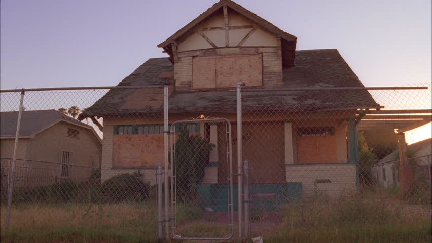 Day Dilapidated boarded up run down lower class two story house dormer right, lot overgrown weeds, surrounded chain link fence sign No Trespass sun low sky behind house dolly right palm tree edge fram