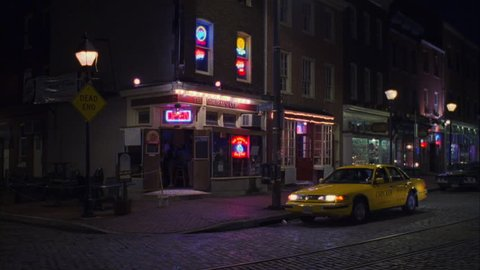Night Pan right ND bar parked taxi cab corner along quaint cobblestone street, small businesses stores, white cargo van away