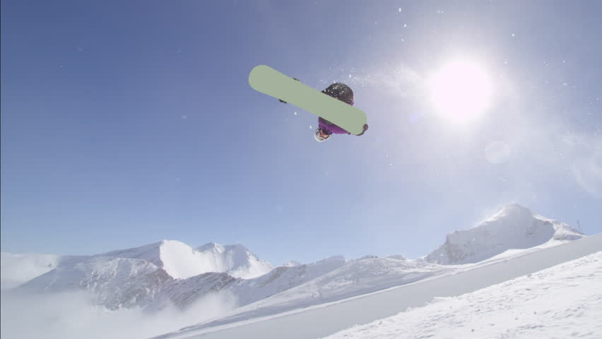 SLOW MOTION: Young pro snowboarder riding the half pipe in big mountain snow park, jumping out of the halfpipe wall and over the sun, performing tricks and rotations with grabs in sunny winter