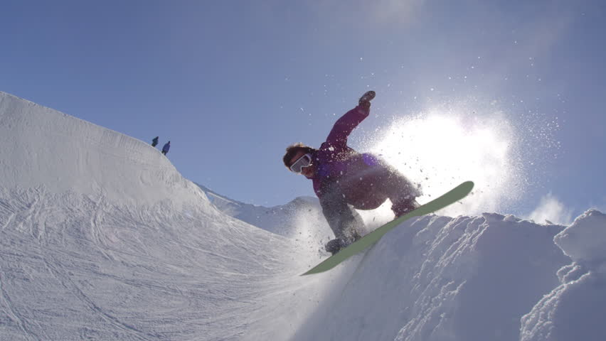 SLOW MOTION: Young pro snowboarder riding the half pipe in big mountain snow park, performing spraying trick over the sun on halfpipe wall in sunny winter