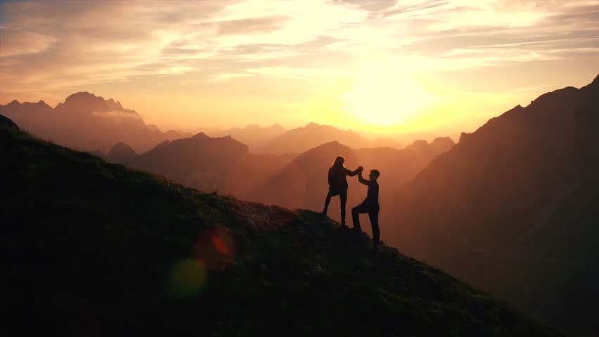 Aerial, edited - Silhouette of a couple giving each other a high five celebrating successful climb on the mountain in beautiful sunset | Shutterstock HD Video #19249195