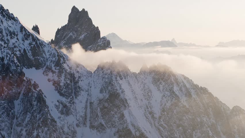 Slow Mo Aerial shot of snowy peaks in the sun with clouds in Courmayeur, Aosta Valley/Italy (Courmayeur, Aosta Valley/Italy - March, 2016)