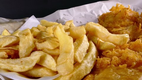 Dolly shot of a very British takeaway meal of fish and chips, with a hand dipping into the optional curry sauce.