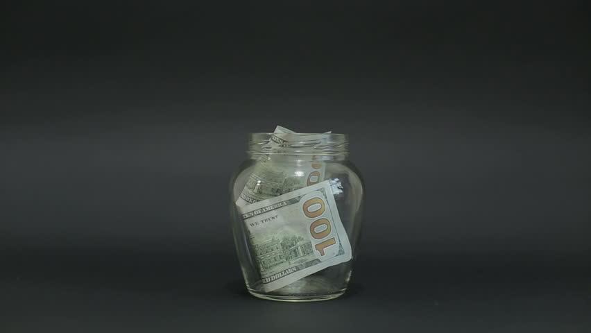 Man Puts American Dollar 100 into a Glass Jar for Storage. Slot glass jar on black background.  | Shutterstock HD Video #19340698