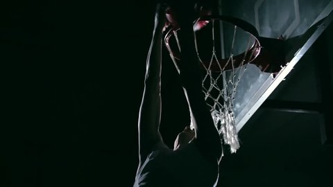 Low angle of reverse dunk performing by professional basketball player in dark court in slow motion