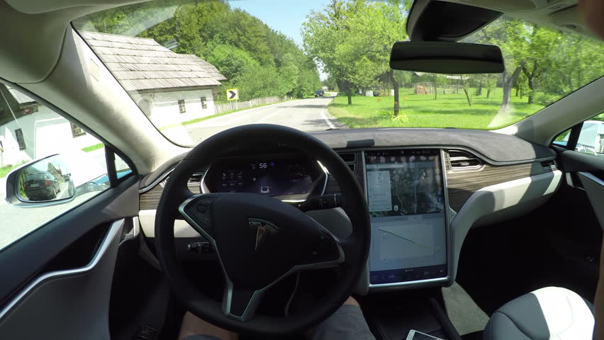 KRANJSKA GORA, SLOVENIA - JULY 17: Tesla self driving autonomous electric car, navigating and steering without driver on local countryside road in village surrounded by lush overgrown rocky mountains