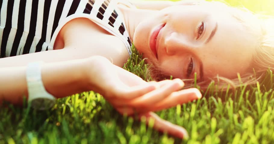 Beautiful young woman lying on the meadow smiling and dreaming. Slow Motion. Enjoy nature. Beauty girl on the green grass outdoors turning to the camera, close up. Spring or summer lawn. Lens flare. #19358578