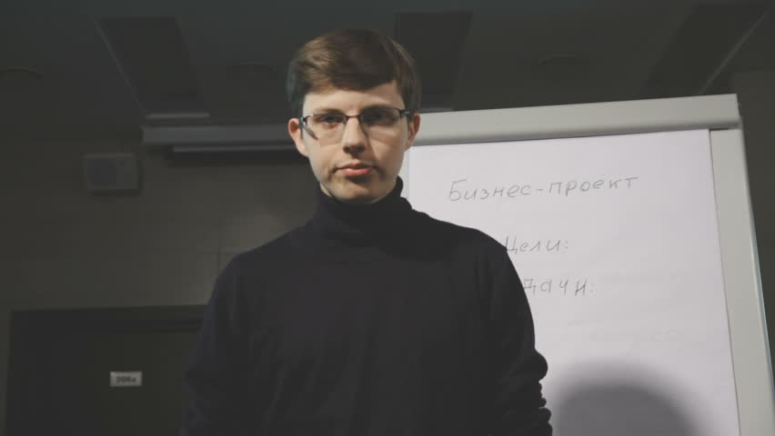 Handsome young businessman pointing at flipchart during presentation in conference room. Presentation speech with flipchart in office. Handsome young man pointing at flipchart while giving
