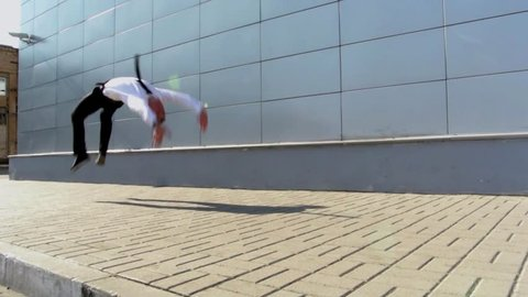 Acrobatic tracer in business suit showing off his flexibility by jumping and doing flips in slow motion