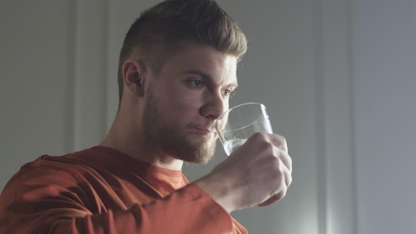 Young man swallowing a pill with water and drinks
