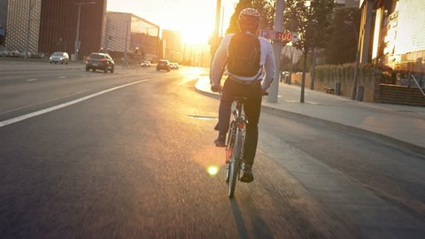 Commuter riding a bike on his morning travel to job. Smartly dressed active young man traveling to job in the city early in the morning. Sunrise in front of the cyclist.