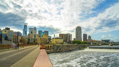 Minneapolis Skyline Stone Arch Bridge Time Lapse Logos Removed 1080p 4k - Stone arch bridge in Minneapolis time lapse with water and buildings. Skyline view with people minnesota