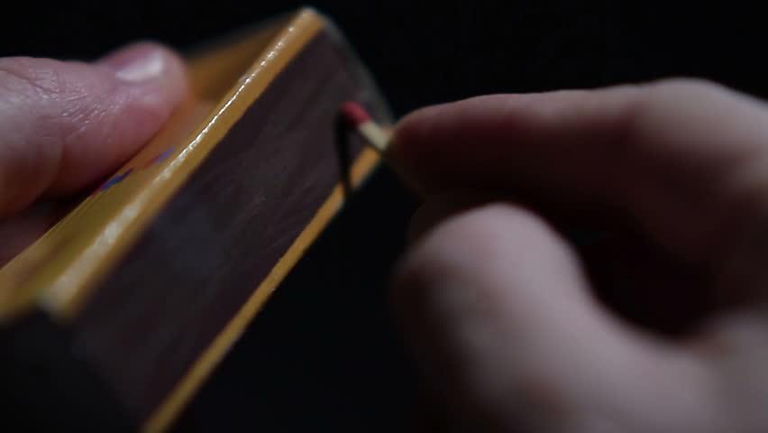 Close up of hands lighting a match.