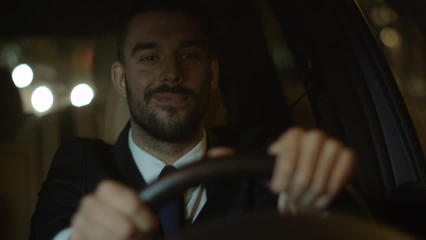 Happy Smiling Businessman Driving a Car through Streets of Night City. Shot on RED Cinema Camera in 4K (UHD). | Shutterstock HD Video #19484287