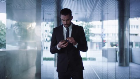 Businessman Walking on Streets of Business District and using Mobile Phone. Shot on RED Cinema Camera in 4K (UHD).