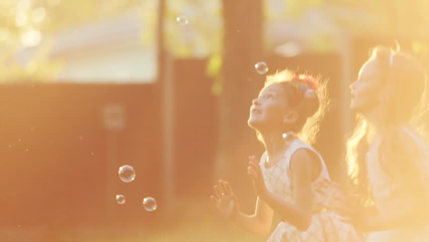Little European children are jumping and playing with the soap bubbles in a sunset light. Lens flare, outside shooting, the restaurant on the background. Portrait. Party atmosphere.