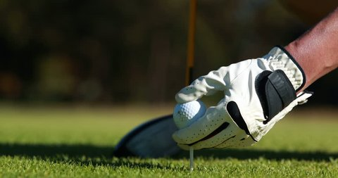 Golfer placing golf ball on tee at golf course 4k