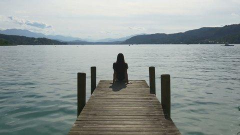 Alpine mountain lake. Woman sitting on wooden pier looking into the distance. Ducks swim near her