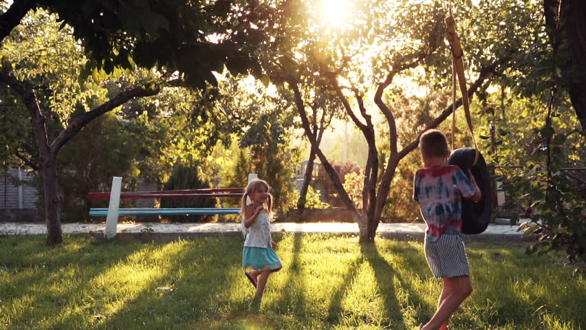 Slow motion of happy girl and boy playing at park with tire swing hanging from tree with beautiful sunlight in background