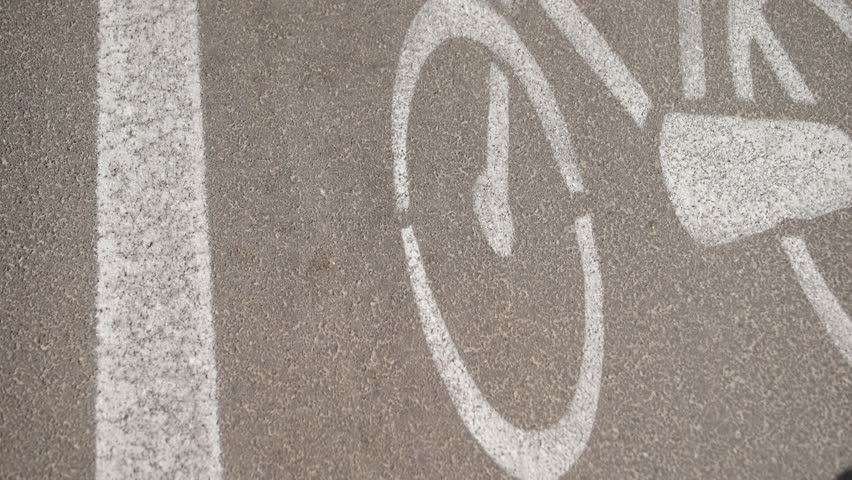 From the top shot of bike path while a bike shadow passing on its white bike symbol. | Shutterstock HD Video #19519678