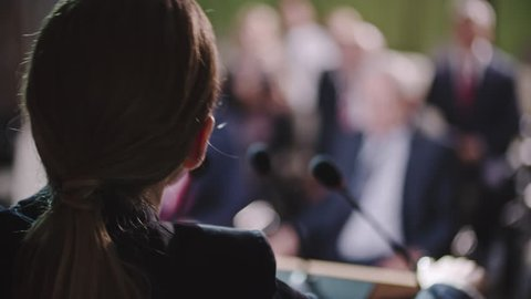 Over the shoulder shot with selective focus of female politician speaking before applauding audience with cameras flashing around her
