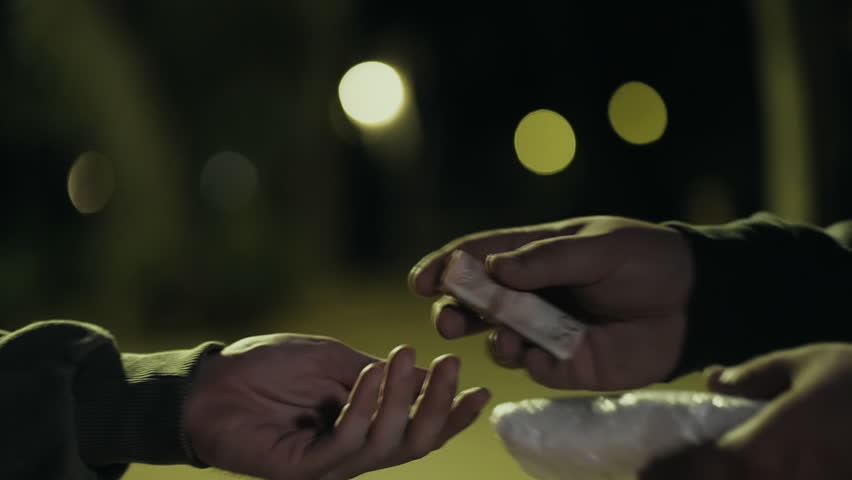 Two hands in dark park selling buying drugs hands cu transaction slow motion.Two men in a dark park at night exchange drugs hand to hand for money.Euro bills.   Shutterstock HD Video #19537558