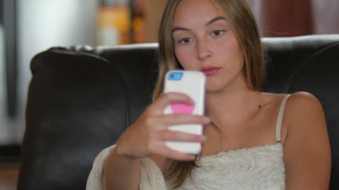 A young blond haired woman takes selfies of herself while sitting in a chair with her smart phone