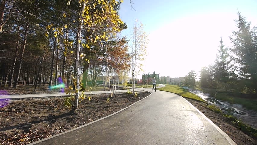 Girl runs through the park in the morning