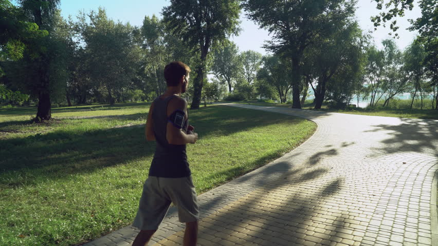 jogger jogging in the morning outdoors, rear back view. adult man using smartphone listen music wearing in t-shirt and sneakers running in the park, where walking man with dogs