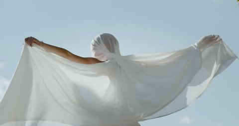 Dancer expressing herself with neo classical dance moves. Ballet trained dancer. Using a white satin sheet against the blue sky with water in the background. Shot in slow motion in an artistic way.