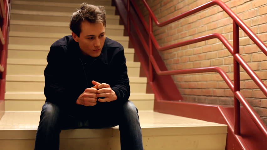 Upset man thinking while sitting on steps