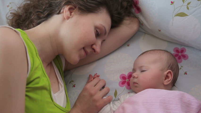 Mom kisses a sleeping baby