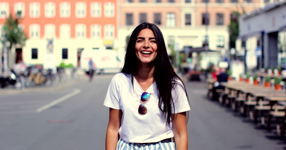 Woman laughing and smiling at camera, standing in big city urban environment
