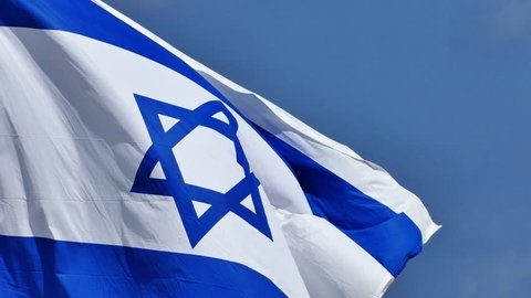 National flag of israel waving in the wind, with blue sky in the background