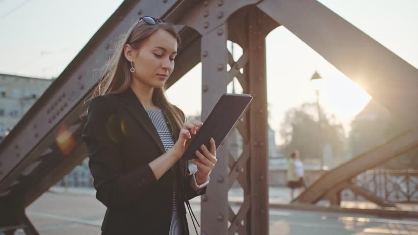 Young Businesswoman Using Digital Tablet, Going to Work in the Sunny Morning City. SLOW MOTION. STEADICAM Stabilized Shot. Attractive Professional Business Woman rushing to a meeting. Lens Flare.