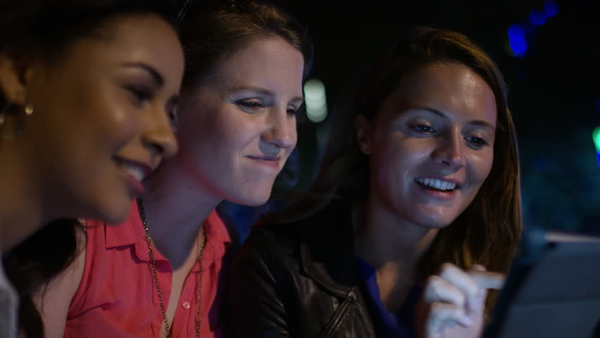 4K Female friends laugh together as they share things on their phones and tablet