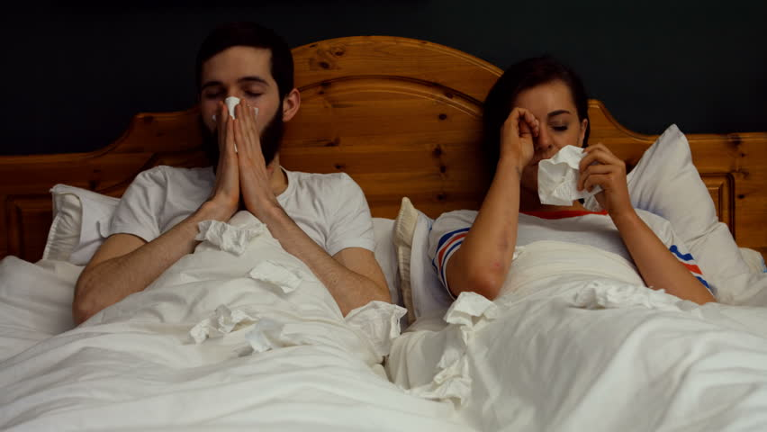 Couple covering nose while sneezing on bed in bedroom at home