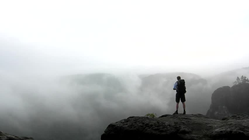 Alone tourist with big backpack stand on cliff edge and watching into deep valley bellow. spring weather.   | Shutterstock HD Video #19694860