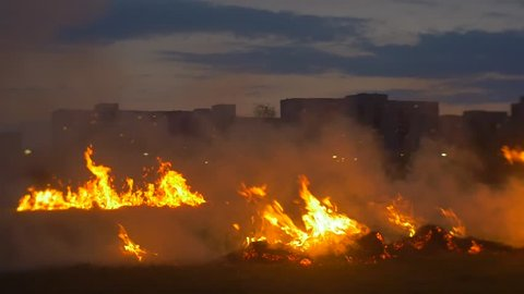 Streaks of Fire For Stunt Riders on Horseback. the Smoke From the Fire on the Field. Bright Flames From Burning Strips of Hay at Twilight.
