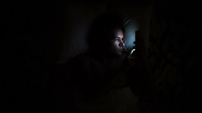 Man in bed turns on phone. Using smartphone in bed due to insomnia health issue. Waking up and using cell phone on pillow in darkness.