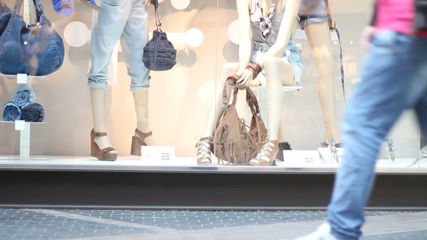 Clothes shop display window with people passing