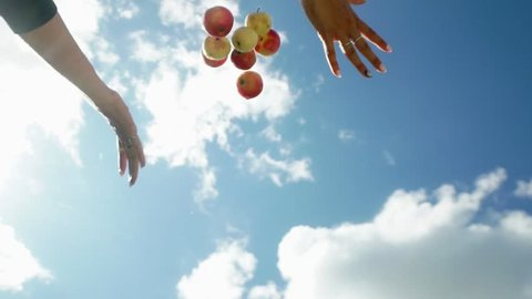 Female hand throw up apples on a background of blue sky. Apples are falling down. Red ripe apples. Slowmotion