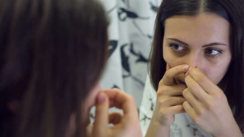 Woman squeezing pimples